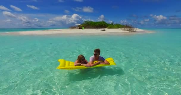 v07267 4k Maldives white sandy beach 2 people young couple man woman floating on airbed inflatable mattress swimming splashing on sunny tropical paradise island with aqua blue sky sea water ocean