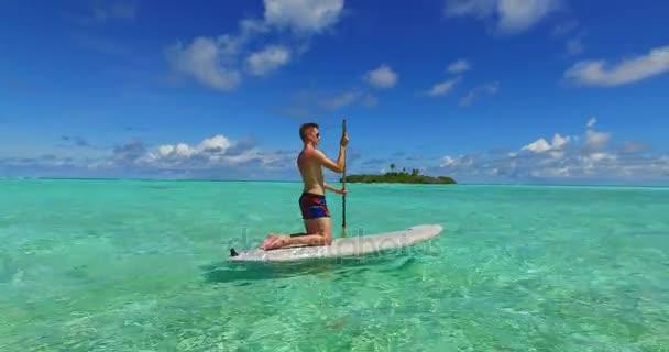 v07276 Maledivy pláž s bílým pískem 2 osoby mladý pár muž žena pádlování veslování na slunečné tropické paradise island s aqua blue sky moře vody oceánu 4k