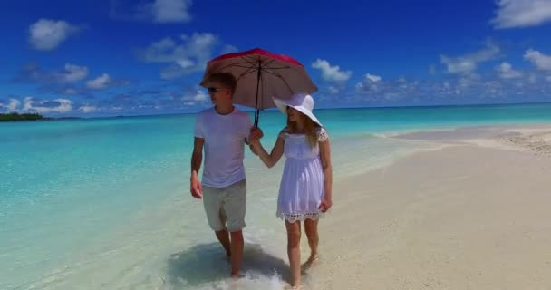 v07514 Maldives white sandy beach 2 people a young couple man woman walking together in love on sunny tropical paradise island with aqua blue sky sea water ocean 4k