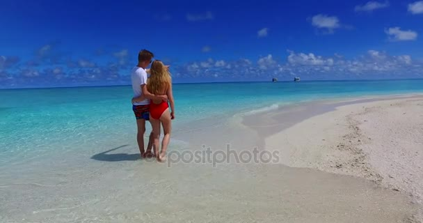 v07533 Maldives white sandy beach 2 people a young couple man woman walking together in love on sunny tropical paradise island with aqua blue sky sea water ocean 4k