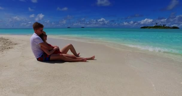 v07410 Maldives white sandy beach 2 people a young couple man woman sitting together on sunny tropical paradise island with aqua blue sky sea water ocean 4k