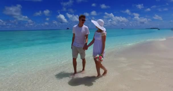 v07491 Maldives white sandy beach 2 people a young couple man woman walking together in love on sunny tropical paradise island with aqua blue sky sea water ocean 4k