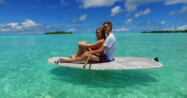v07309 Maldives white sandy beach 2 people young couple man woman paddleboard rowing on sunny tropical paradise island with aqua blue sky sea water ocean 4k