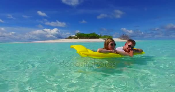 v07263 4k Maldives white sandy beach 2 people young couple man woman floating on airbed inflatable mattress swimming splashing on sunny tropical paradise island with aqua blue sky sea water ocean