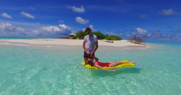 v07250 4k Maldives white sandy beach 2 people young couple man woman floating on airbed inflatable mattress swimming splashing on sunny tropical paradise island with aqua blue sky sea water ocean