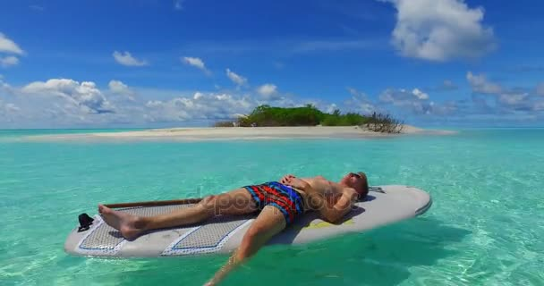 v07376 Maldives white sandy beach 2 people young couple man woman paddleboard rowing on sunny tropical paradise island with aqua blue sky sea water ocean 4k