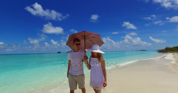 v07511 Maldives white sandy beach 2 people a young couple man woman walking together in love on sunny tropical paradise island with aqua blue sky sea water ocean 4k