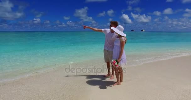 v07492 Maldives white sandy beach 2 people a young couple man woman walking together in love on sunny tropical paradise island with aqua blue sky sea water ocean 4k