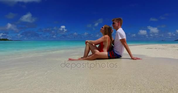 v07420 Maldives white sandy beach 2 people a young couple man woman sitting together on sunny tropical paradise island with aqua blue sky sea water ocean 4k