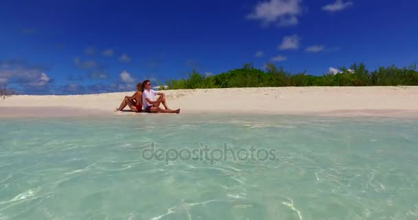 v07398 Maldives white sandy beach 2 people a young couple man woman sitting together on sunny tropical paradise island with aqua blue sky sea water ocean 4k
