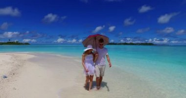 V07506 Maldives white sandy beach 2 people a young couple man woman walking together in love on sunny tropical paradise island with aqua blue sky sea water ocean 4k