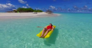 V07251 4k Maldives white sandy beach 2 people young couple man woman floating on airbed inflatable mattress swimming splashing on sunny tropical paradise island with aqua blue sky sea water ocean
