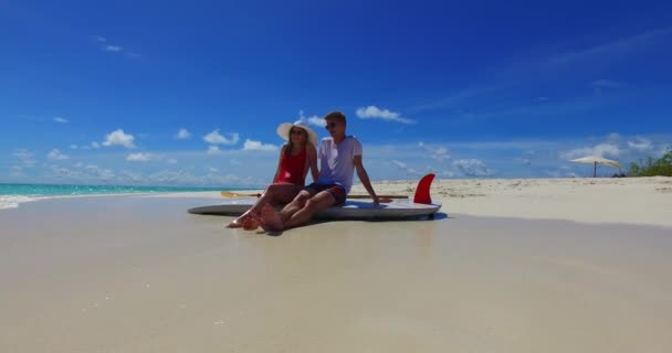 v07442 Maldives white sandy beach 2 people a young couple man woman sitting together on sunny tropical paradise island with aqua blue sky sea water ocean 4k