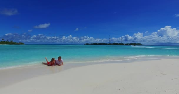 v07259 4k Maldives white sandy beach 2 people young couple man woman floating on airbed inflatable mattress swimming splashing on sunny tropical paradise island with aqua blue sky sea water ocean