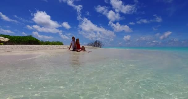 v07412 Maldives white sandy beach 2 people a young couple man woman sitting together on sunny tropical paradise island with aqua blue sky sea water ocean 4k