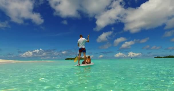v07274 Maldives white sandy beach 2 people young couple man woman paddleboard rowing on sunny tropical paradise island with aqua blue sky sea water ocean 4k