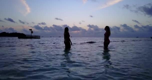 25b5a8c56c V10777 zwei 2 schöne junge Mädchen bei Sonnenuntergang Sonnenaufgang  plantschen am Strand abends mit Wasser und sand– Stock-Filmmaterial