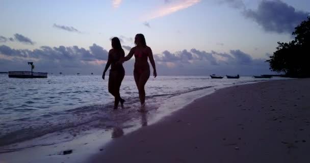 9bf0ba2cbc V10784 zwei 2 schöne junge Mädchen bei Sonnenuntergang Sonnenaufgang  plantschen am Strand abends mit Wasser und sand– Stock-Filmmaterial