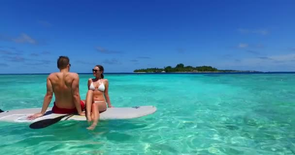 v11368 two 2 people romantic young people couple paddleboard surfboard with drone aerial flying view on a tropical island of white sand beach and blue sky and sea