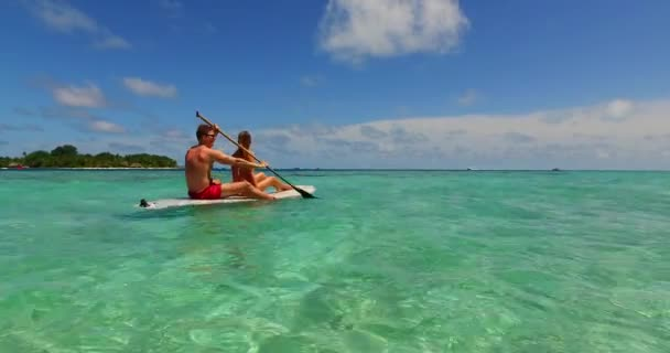 v11300 two 2 people romantic young people couple paddleboard surfboard with drone aerial flying view on a tropical island of white sand beach and blue sky and sea