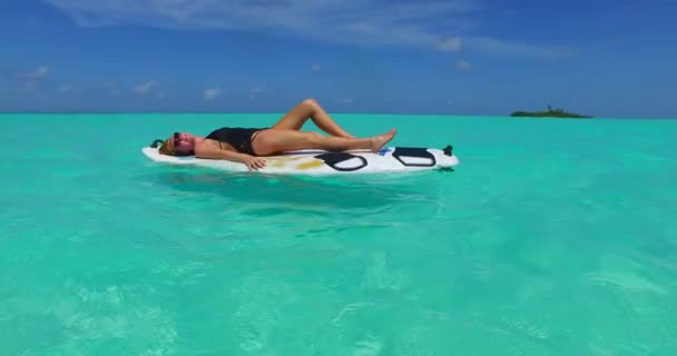 v11989 one 1 beautiful young girl in bikini sunbathing on surfboard paddleboard and relaxing by the aqua blue sea water on white sand in the sun