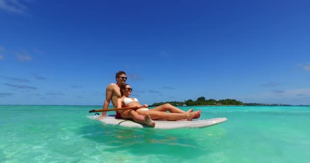 v11375 two 2 people romantic young people couple paddleboard surfboard with drone aerial flying view on a tropical island of white sand beach and blue sky and sea