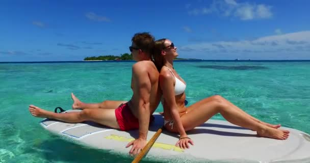 v11317 two 2 people romantic young people couple paddleboard surfboard with drone aerial flying view on a tropical island of white sand beach and blue sky and sea