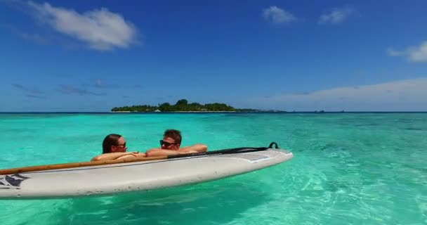 v11377 two 2 people romantic young people couple paddleboard surfboard with drone aerial flying view on a tropical island of white sand beach and blue sky and sea