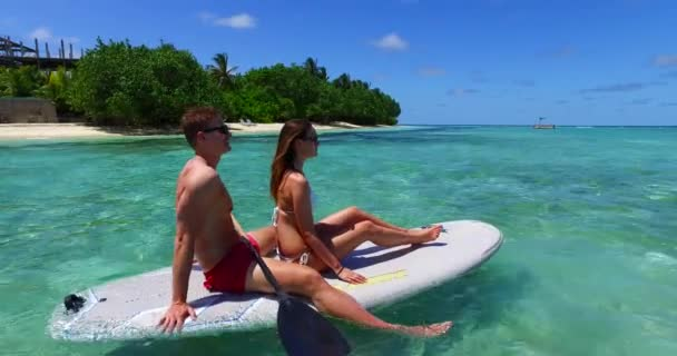 v11310 two 2 people romantic young people couple paddleboard surfboard with drone aerial flying view on a tropical island of white sand beach and blue sky and sea