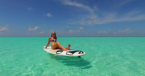 v11939 egy 1 szép, fiatal lány a bikini napozásra a szörfdeszka paddleboard, és pihentető a aqua kék tenger víz a fehér homok, a nap
