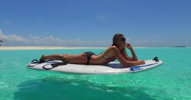 v11949 egy 1 szép, fiatal lány a bikini napozásra a szörfdeszka paddleboard, és pihentető a aqua kék tenger víz a fehér homok, a nap