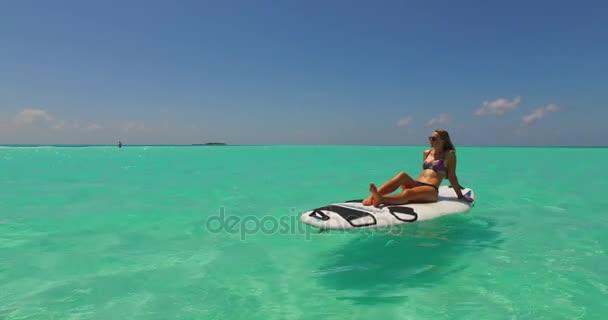 v11947 egy 1 szép, fiatal lány a bikini napozásra a szörfdeszka paddleboard, és pihentető a aqua kék tenger víz a fehér homok, a nap
