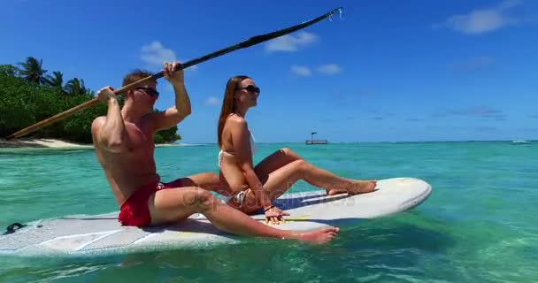 v11297 two 2 people romantic young people couple paddleboard surfboard with drone aerial flying view on a tropical island of white sand beach and blue sky and sea