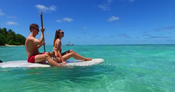v11352 two 2 people romantic young people couple paddleboard surfboard with drone aerial flying view on a tropical island of white sand beach and blue sky and sea