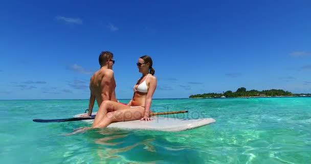 v11362 two 2 people romantic young people couple paddleboard surfboard with drone aerial flying view on a tropical island of white sand beach and blue sky and sea