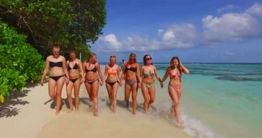 V12801 walking and sunbathing group of young beautiful girls on white sand beach in aqua blue clear sea water and sky