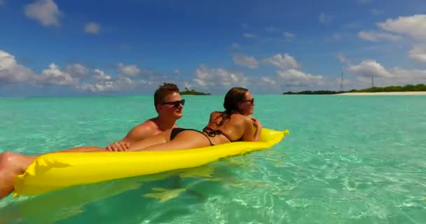 v13893 two 2 people inflatable sunbed romantic young people couple with drone aerial flying view on a tropical island of white sand beach and blue sky and sea