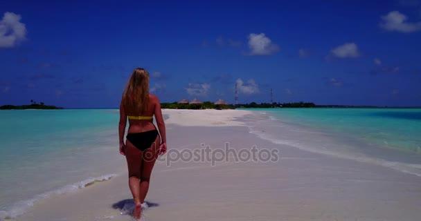 v13752 egy szép, fiatal lány a bikini napozásra, és séta a aqua kék tenger víz fehér homok, a nap