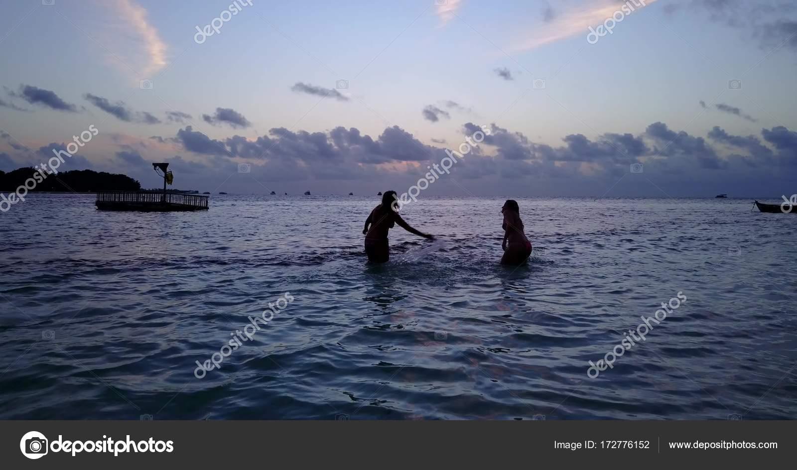 024c5507d1 V10782 zwei 2 schöne junge Mädchen bei Sonnenuntergang Sonnenaufgang  plantschen am Strand abends mit Wasser und