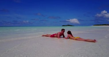 V14842 two 2 people laying romantic young couple sunbathing on a tropical island of white sand beach and blue sky and sea