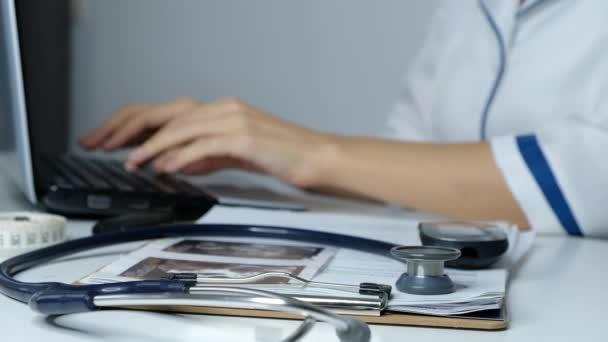 Ärztin arbeitet am Computer, tippt auf Laptop, füllt Daten aus nächster Nähe