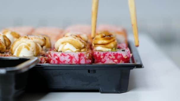 Lieferservice-Konzept: Frau isst Sushi-Rollen aus Plastikbox, hautnah