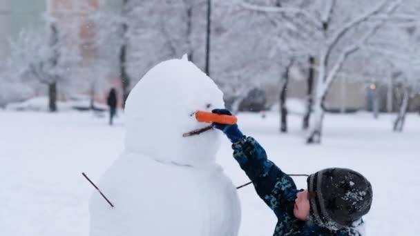 Dítě se sněhulákem v zimě zasněžený den, vánoční svátky