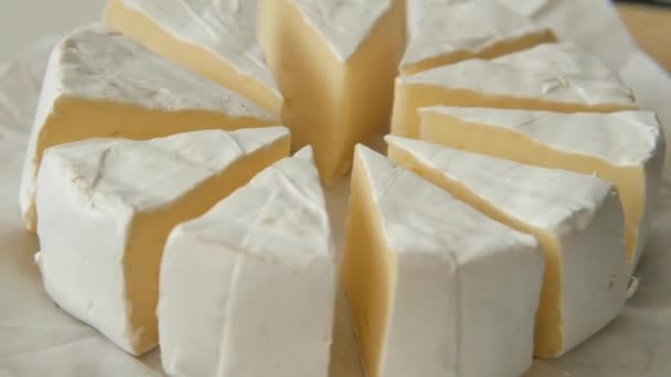 Sliced sectors of soft cheese brie or camambert rotating, close up