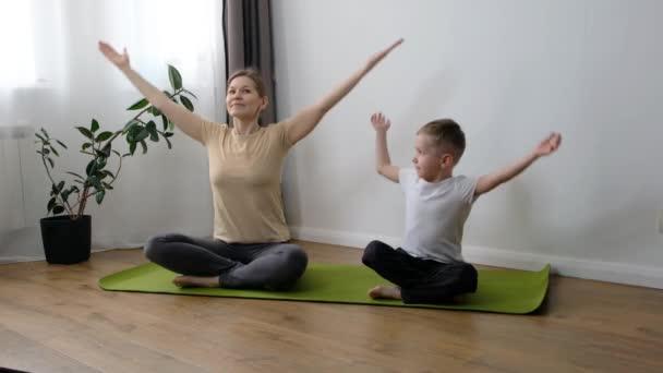 Eine Mutter mittleren Alters macht zu Hause mit ihrem kleinen Sohn Yoga-Übungen. Gesunder Lebensstil