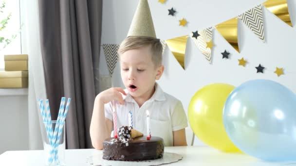 Boldog kisfiú ünnepli a születésnapját egyedül ül az asztal előtt, és gyertyákat fúj a tortán.