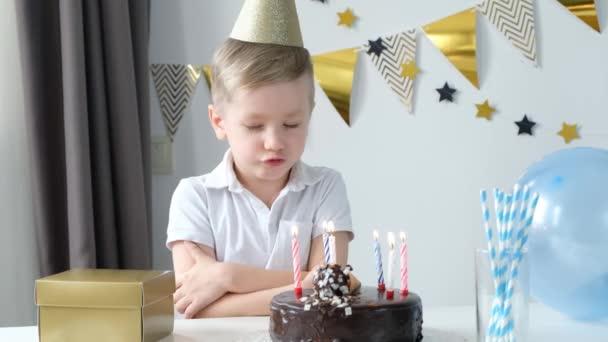Ideges kisfiú, aki a születésnapját ünnepli, egyedül ül a torta előtt gyertyagyújtással, szomorúsággal és boldogtalansággal..