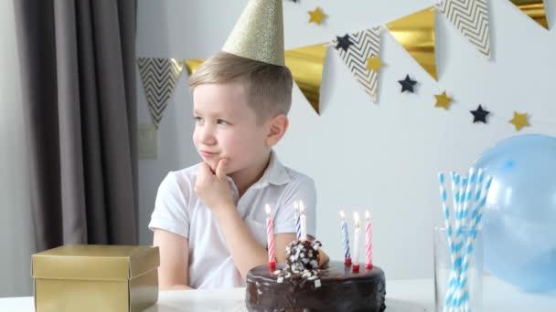 Šťastný chlapec slaví narozeniny, přání a foukání svíčky na dort