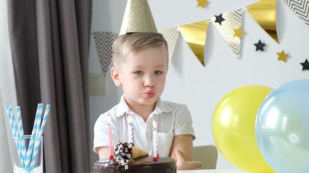 Boldogtalan, szomorú fiú egyedül ünnepli a születésnapját és gyertyákat fúj a tortán.