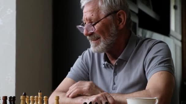 Malý chlapec hraje šachy se svým dědečkem, starší pozitivní muž